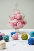 Balls of wool of various colours on table & in glass jar