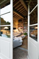 View through open French doors into comfortable living room with large bookcase below rustic wooden ceiling