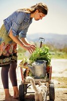 Young woman with farm produce on hand cart