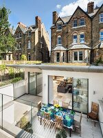Modern extension of Victorian country house with green roof, sunken living area and terrace with glass balustrade