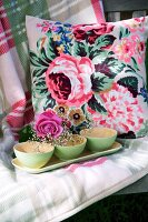 Gypsophila in green bowls and rose on tray in front of cushion with rose motif on checked blanket