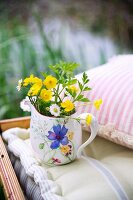Small painted jug of wild flowers on seat cushion next to pink and white striped scatter cushion