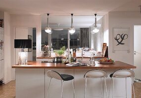 Bar stools at white counter with wooden worksurface; table lamp with black lampshade to one side and pendant lamps with spherical lampshades above kitchen counter