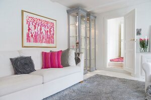 Feminine interior in white and grey with pink accents; illuminated display cabinet next to modern artwork and sofa