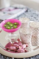 Flowers in pink goblet, silvery tealight holders and sweets on shiny tray