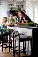 Young family around counter with bar stools in open-plan kitchen