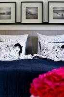 Scatter cushions with comic-style covers on bed with upholstered headboard below framed pictures on wall