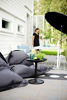Black beanbags and side table in front of table under black parasol and woman in terrace door