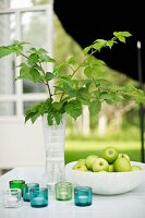 Vase of leafy twigs and bowl of green apples behind tealight holders on garden table