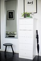 Narrow, white chest of drawers, black umbrella and stool on black tiled floor in hall