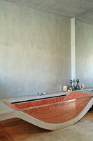 Bathtub made from curved concrete slab and glass side wall with red mosaic tiles inside in minimalist bathroom