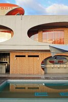 Hotel Cocoon in Salvador, Bahia, Brazil with oval apertures in concrete facade, wood panelling and pool in foreground