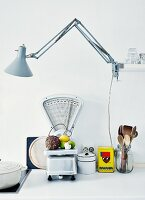 Vintage arrangement of old scales from flea market, exotic tin cans and retro clip lamp on kitchen worksurface