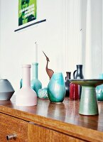 Danish candlesticks and collection of small ceramic vases from flea-market on 60s, retro sideboard