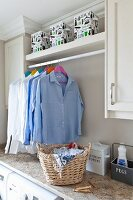 Clothes rack between wall units in laundry room