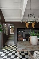 Wooden table in front of fireplace below stylised hunting trophies in dining room with chequered floor tiles