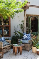 Wicker armchairs with batik cushions, African side table and potted plants on terrace