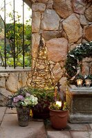 Christmas atmosphere in garden, lit candle in flower pot and obelisk covered in fairy lights in front of stone wall
