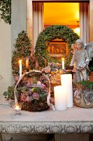 Flower arrangements in wire baskets and lit candles on festively decorated terrace table
