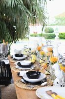 Festively set table on terrace with exotic flower arrangements & china parrots