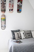 Scatter cushions printed with letters on grey throw on teenager's bed below scuffed skateboards decorating wall