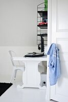 Black and white study area with white designer chair, desk and retro, wall-mounted shelves
