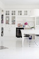 White dining table and classic Eames chairs in front of white dresser in rustic dining room