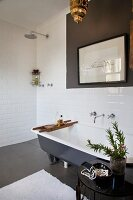 Plant on side table next to free-standing bathtub, framed drawing on wall and floor-level, open shower in corner of white-tiled bathroom