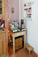 Coffee mill and espresso machine on rustic side table next to wall-mounted spice rack in corner of kitchen