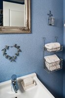 White towels in rack mounted on blue-painted bathroom wall