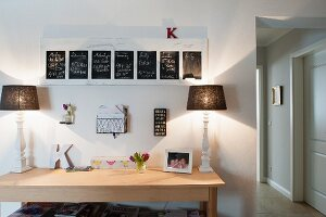 Modern wooden table with two table lamps below framed blackboards on wall