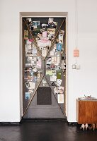 Old steel door used as magnetic pinboard for photos