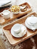 White tea set on wooden trays on ottoman with cowhide cover
