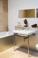 Minimalist washstand with metal frame against projecting wall and bathtub with metal cladding in bathroom with sand-coloured limestone floor