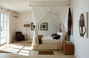 Canopied bed with mosquito nets in hotel room with sparse, African-style furnishings