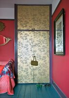 Elegant Chinese pattern in gold on doors of wardrobe contrasting with raspberry walls and petrol-blue floor