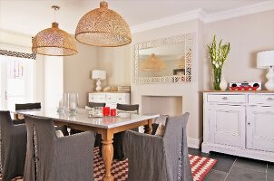 Wooden table with marble top and chairs with grey loose covers below wicker pendant lamps in rustic dining room