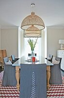 Elegant, grey, loose-covered chairs around dining table below two wicker pendant lamps and rug with red and white zigzag patterns in country-house interior with French windows