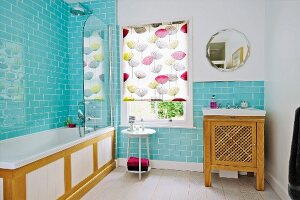 Bathroom with pale blue wall tiles, wood-clad bathtub, patterned roller blind on window and sink on wooden washstand