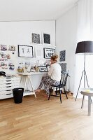 Woman sitting at desk and standard lamp wit black lampshade in home office