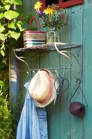 A vintage exterior coat rack with a bunch of flowers on a shelf with a sun hat and garden utensils on hooks