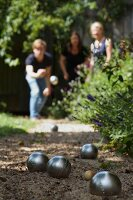Boules balls on a sandy path in a garden with the players out of focus in the background