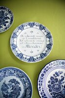 White and blue painted plates on green-painted wall