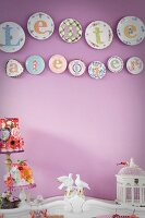 Decorative wall plates on lilac wall above bird figurines on cabinet with curved top