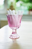 White candles in purple stemmed glass