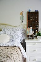 Bed with white curved frame and romantic bed linen next to tiny display case on white bedside cabinet