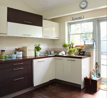 Pale and dark cabinet fronts in simple fitted kitchen with potted herbs and vintage-style lettering