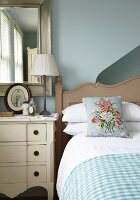 Floral cushion on country-house bed next to chest of drawers and mirror on pale blue wall