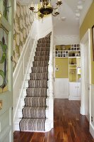 Staircase with striped runner, walls in shades of green and white, fitted wooden elements in hallway