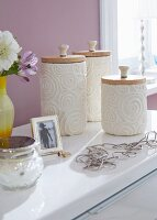 Ceramic pots wrapped in cream-coloured relief paper